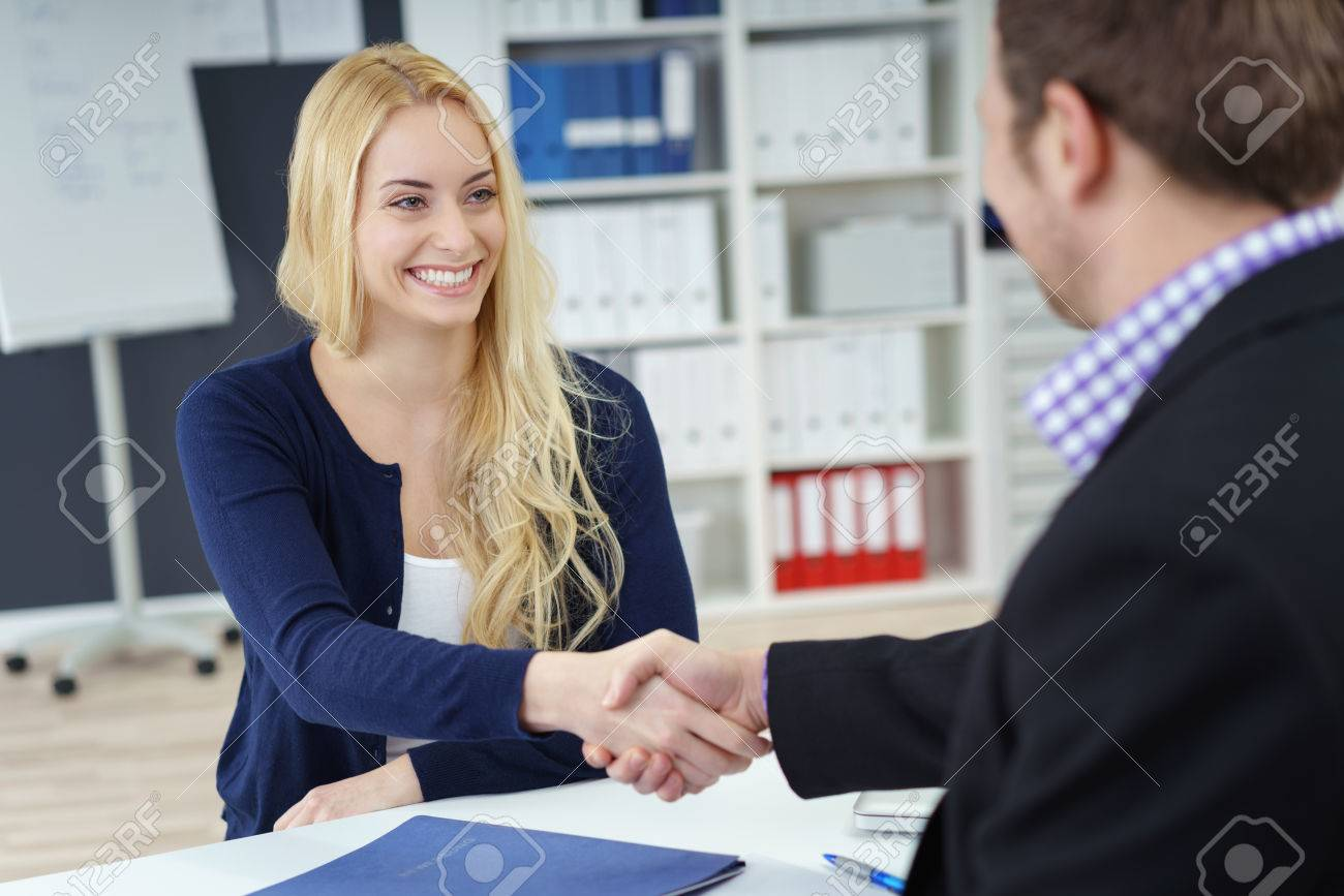 Businessman and woman shaking hands across an office desk as they seal a deal, in partnership, congratulations or in welcome, focus to attractive young woman Stock Photo - 51502204