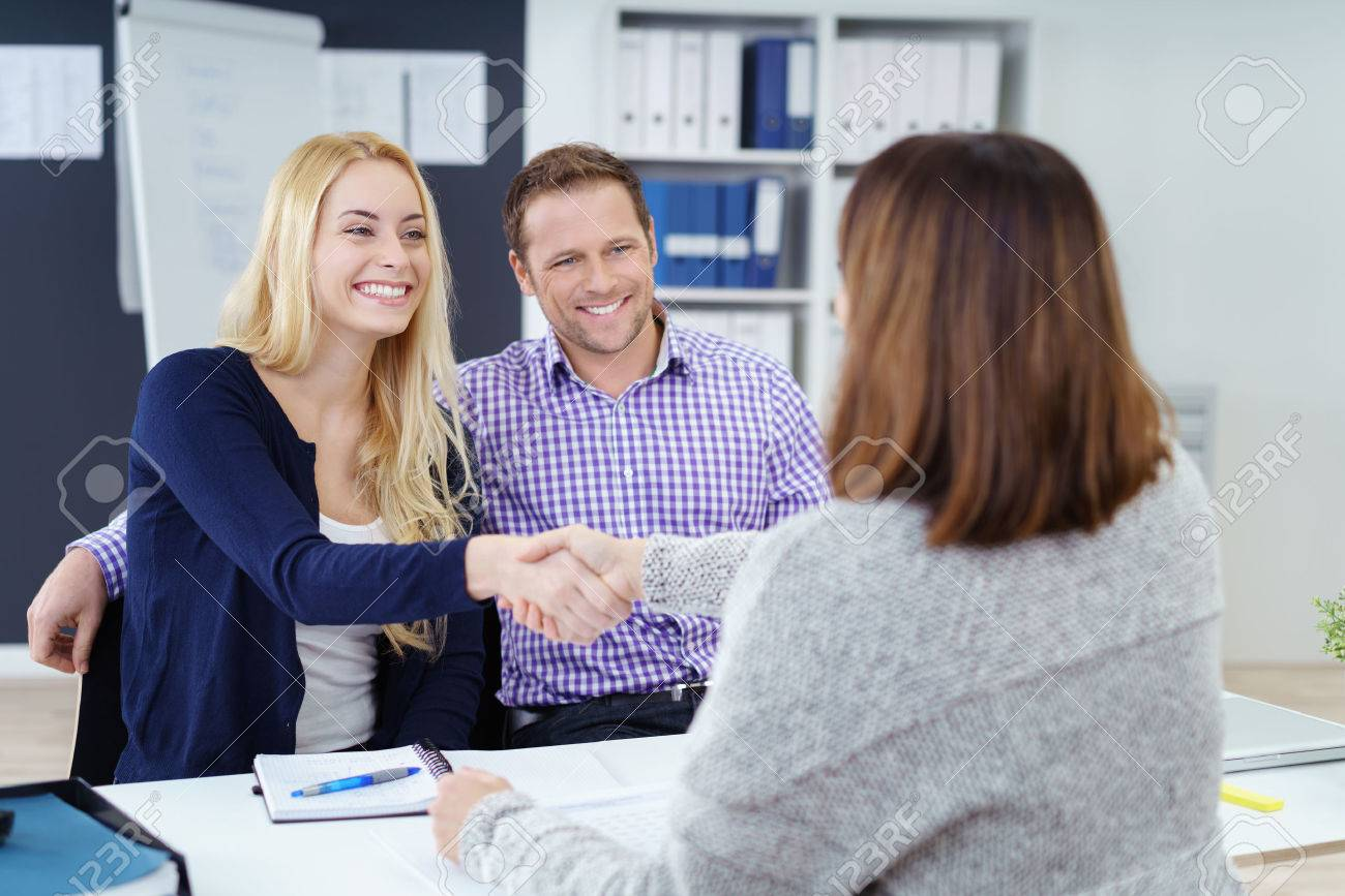 Happy couple shaking hands with a female business broker or investment adviser as they attend a meeting in her office Stock Photo - 51502326