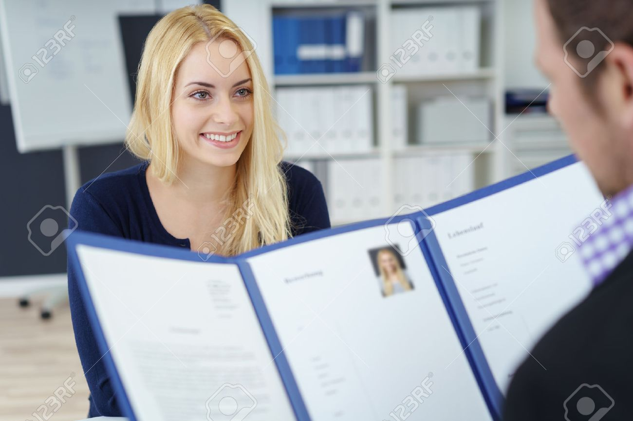 Attractive young businesswoman in a job interview with a corporate personnel manager who is reading her CV in a blue folder, over the shoulder focus to the young applicant - 51502424