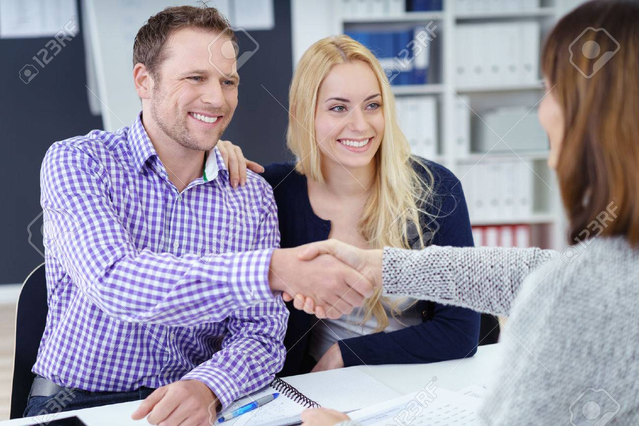 Smiling pleased attractive young couple shaking hands with a business broker or adviser as they sit with her in the office in a meeting, view over the advisers shoulder Stock Photo - 51502439