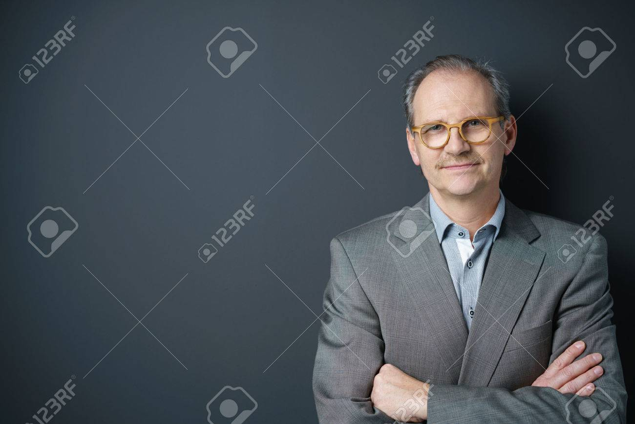 self-conscious middle-aged businessman standing with arms crossed Stock Photo - 51788012