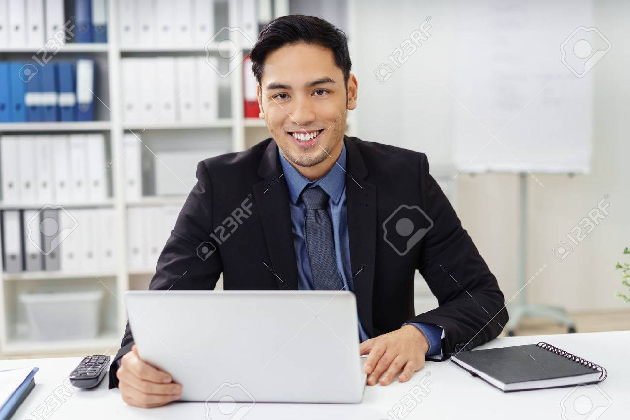 Cute young businessman with goatee looking ahead from behind laptop at desk in office with happy expression Standard-Bild - 52362206