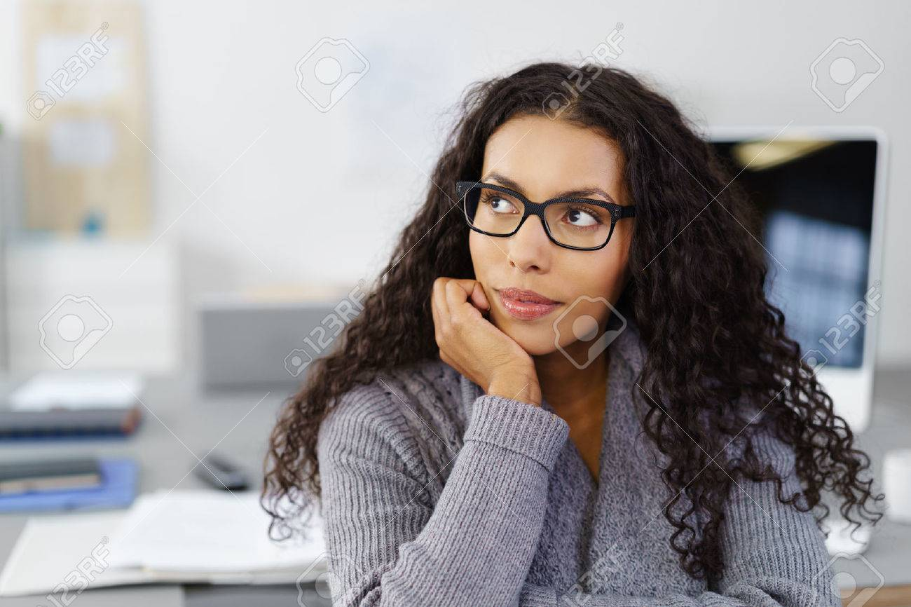 business woman sitting at her desk in the office with her chin on her hand looking up in thoughts Stock Photo - 52361923