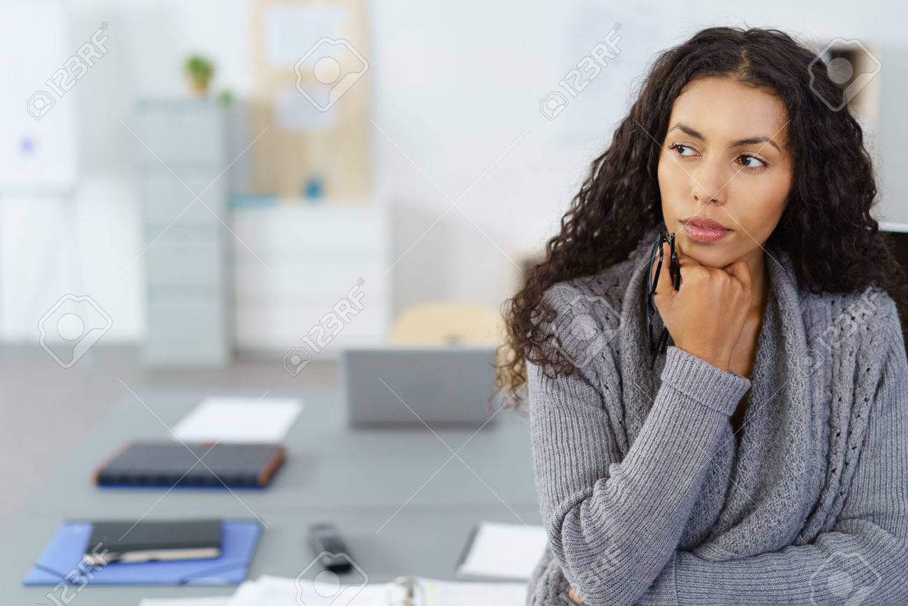 businesswoman with hand on chin sitting at desk in the office in thoughts - 52361866