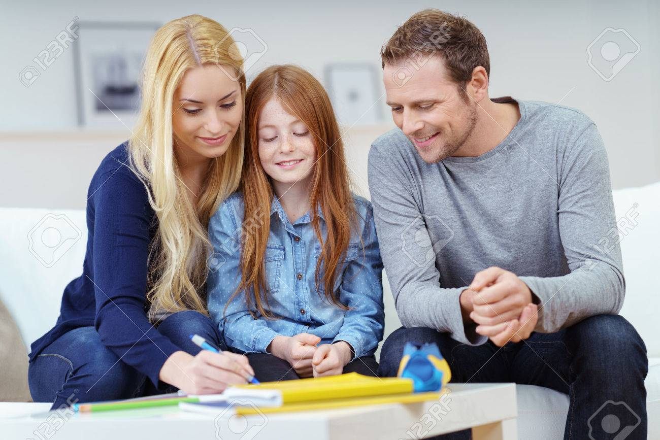 Happy family doing homework together as the parents help their attractive young redhead daughter with her class work on the sofa at home Standard-Bild - 52361704