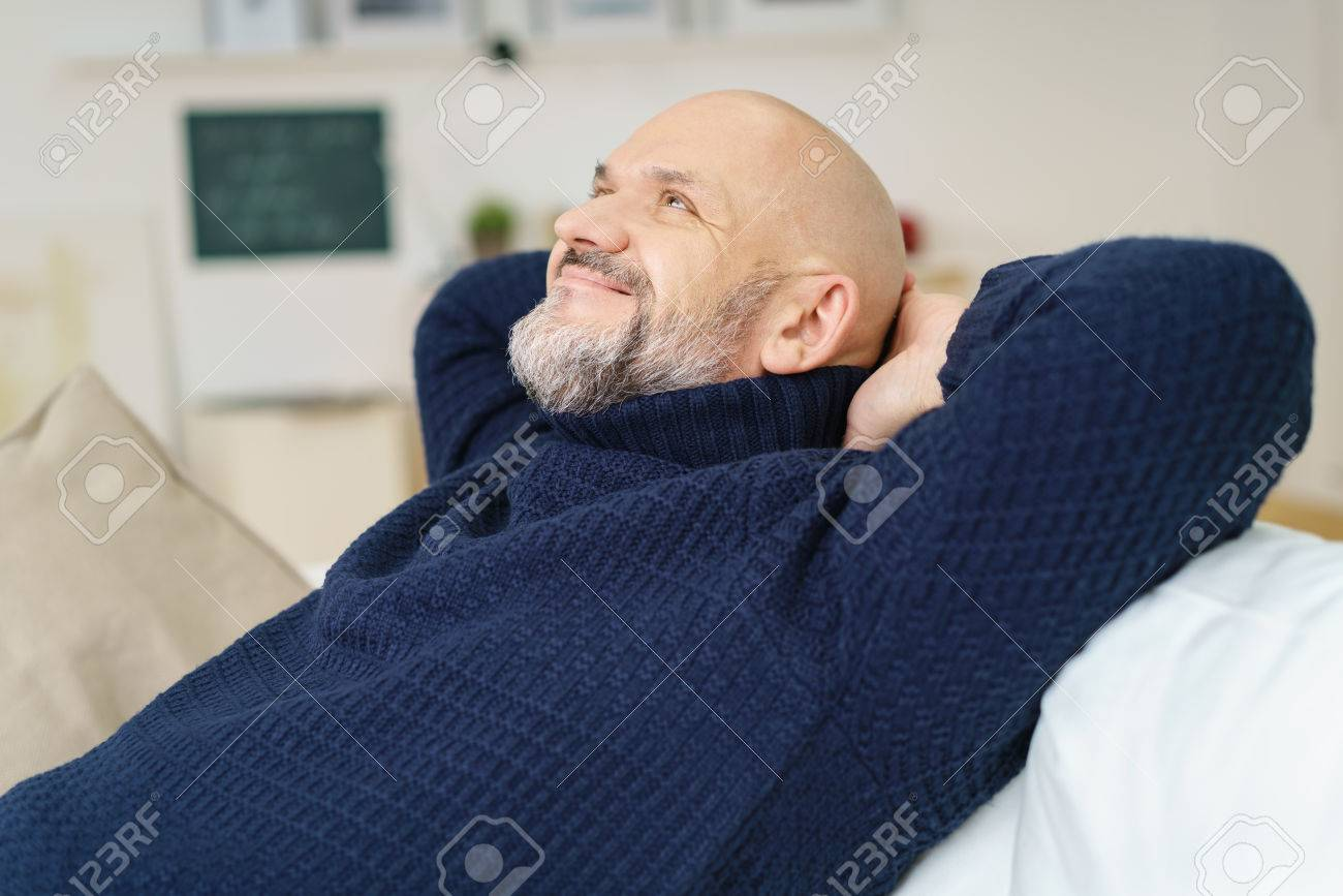 Happy contented middle-aged man with a goatee relaxing at home on the sofa with his hands behind his head smiling with pleasure as he looks up into the air - 54148561