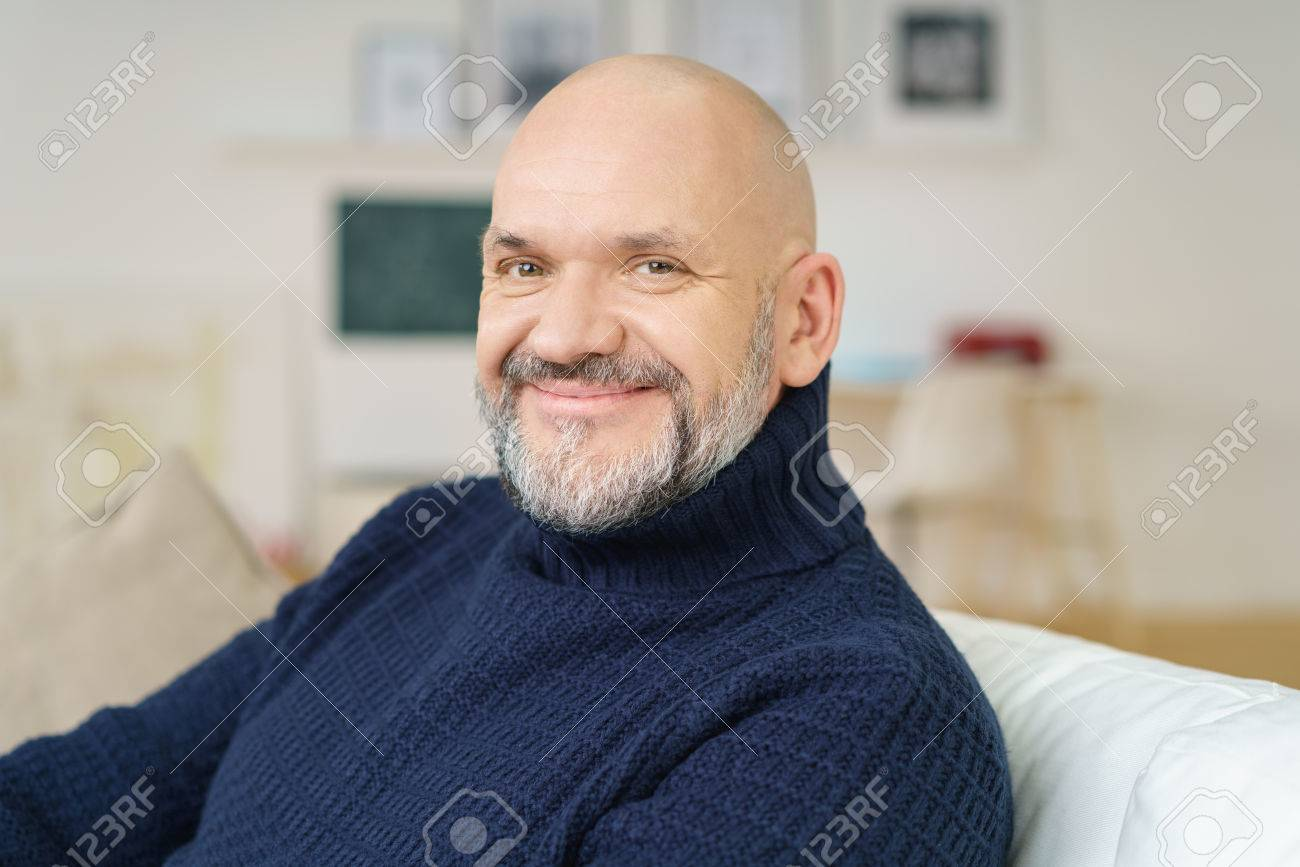 Attractive bald middle-aged man with a goatee sitting relaxing on a couch at home looking at the camera with a lovely wide engaging smile - 54148562