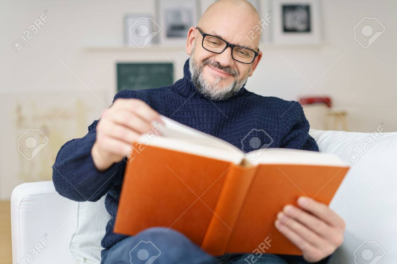 Middle-aged bald man with a goatee wearing glasses sitting on a comfortable couch enjoying a good book with a smile of pleasure - 54148584