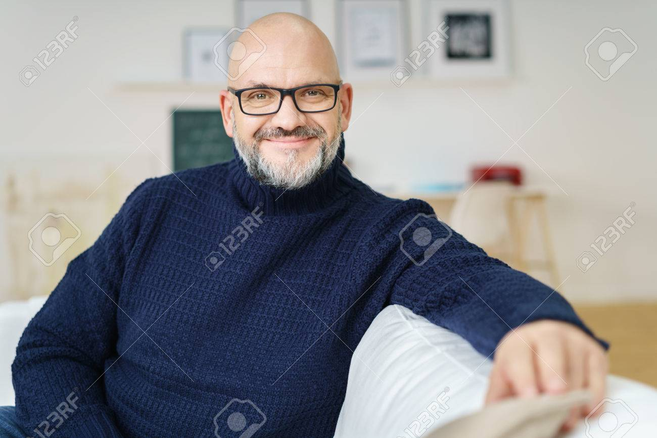 Relaxed attractive bald middle-aged man wearing glasses with a friendly smile sitting on a sofa in his living room smiling at the camera - 54148666