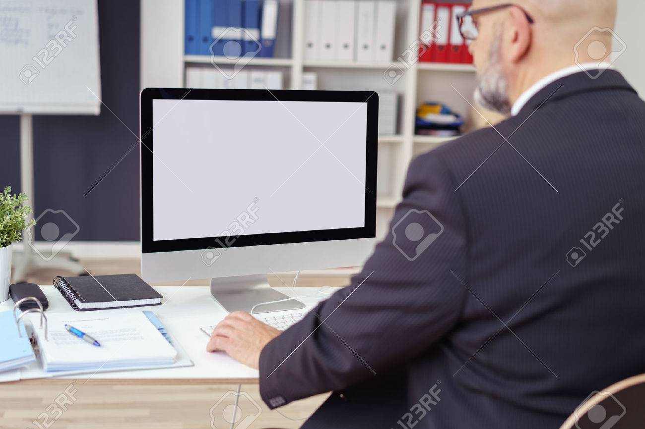 Rear over the shoulder view of a businessman working at his desk in the office with focus to his blank desktop computer monitor Stock Photo - 54148729