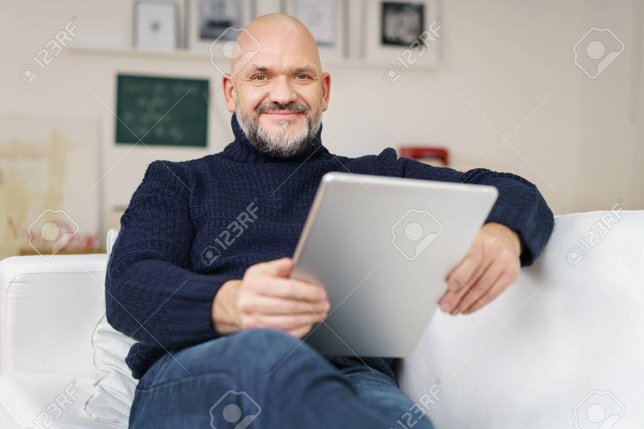 Middle-aged balding man with a goatee and glasses relaxing at home on a comfortable sofa with a tablet computer smiling at the camera Banque d'images - 54148973