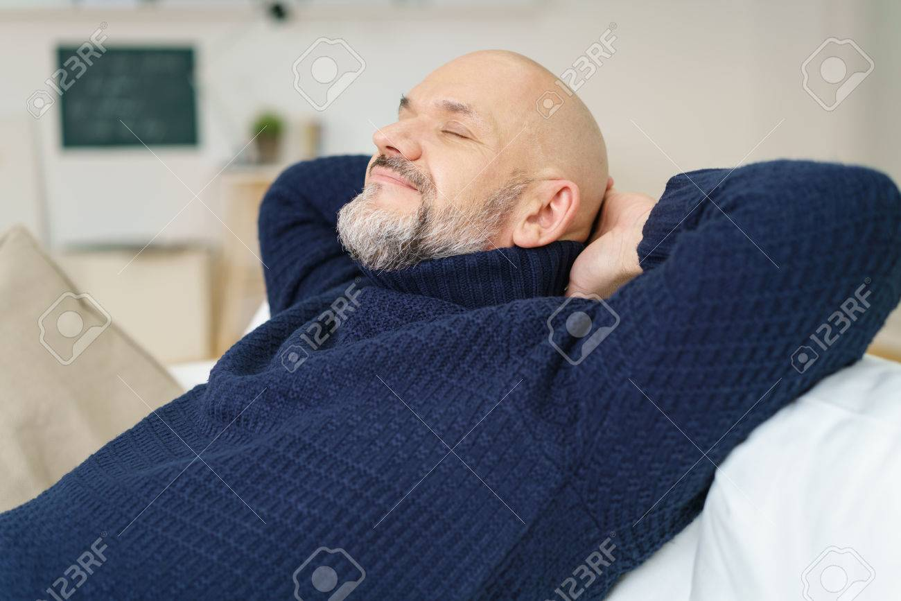 Happy man enjoying a blissful rest sitting on a comfortable sofa clasping his hands behind his neck with his eyes closed and a pleased smile , side view Stock Photo - 54149030