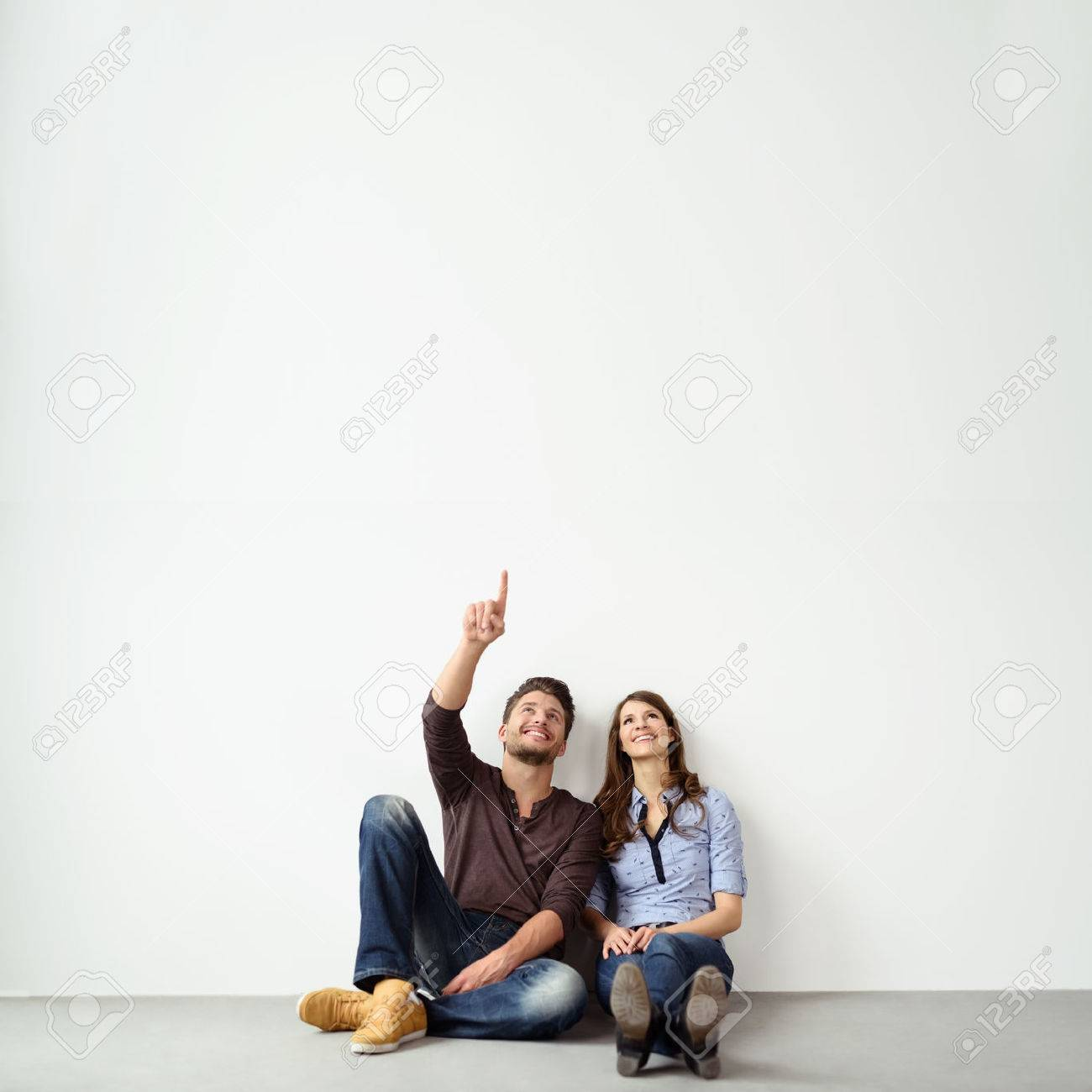 Young couple sitting on the ground leaning against an exterior white all with copy space pointing up into the air and smiling Stock Photo - 54149034