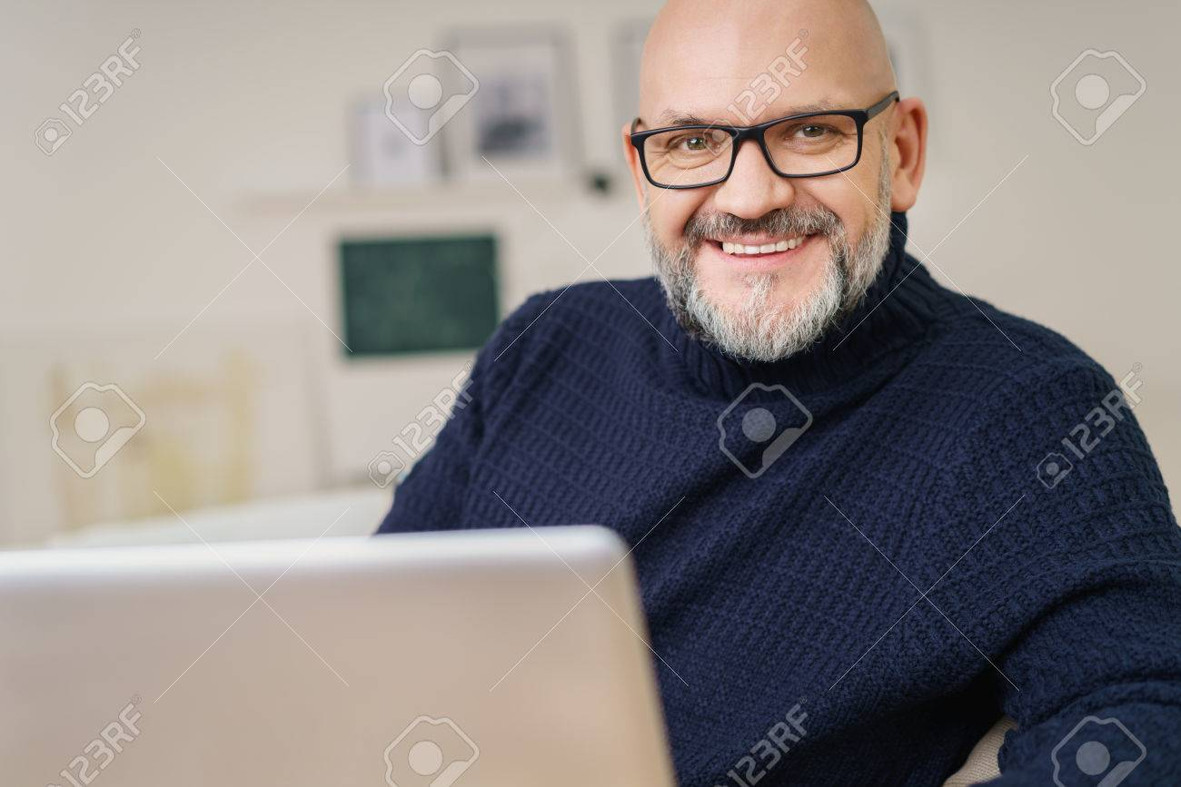 Attractive middle-aged man with a goatee and glasses relaxing at home with his laptop computer looking at the camera with a warm beaming smile - 54149073
