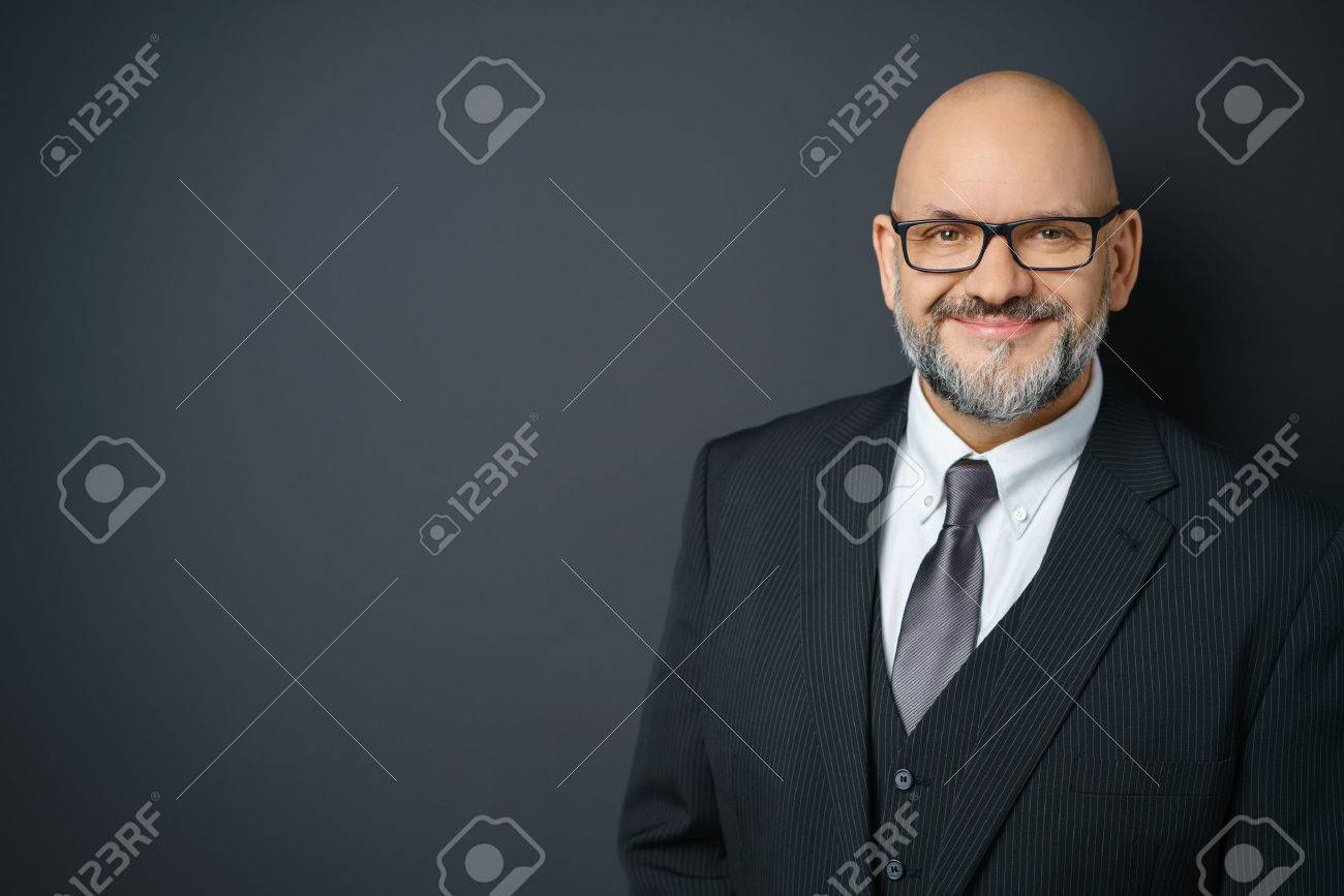 Waist Up Portrait of Mature Businessman with Facial Hair Wearing Suit and Eyeglasses Smiling Confidently at Camera and Standing in Studio with Dark Gray Background with Copy Space Stock Photo - 54149082