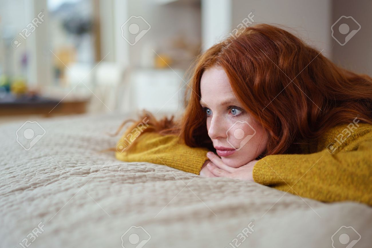 Attractive young redhead woman lying on her bed on her stomach thinking resting her chin on her hands and staring into the distance Banque d'images - 54149137