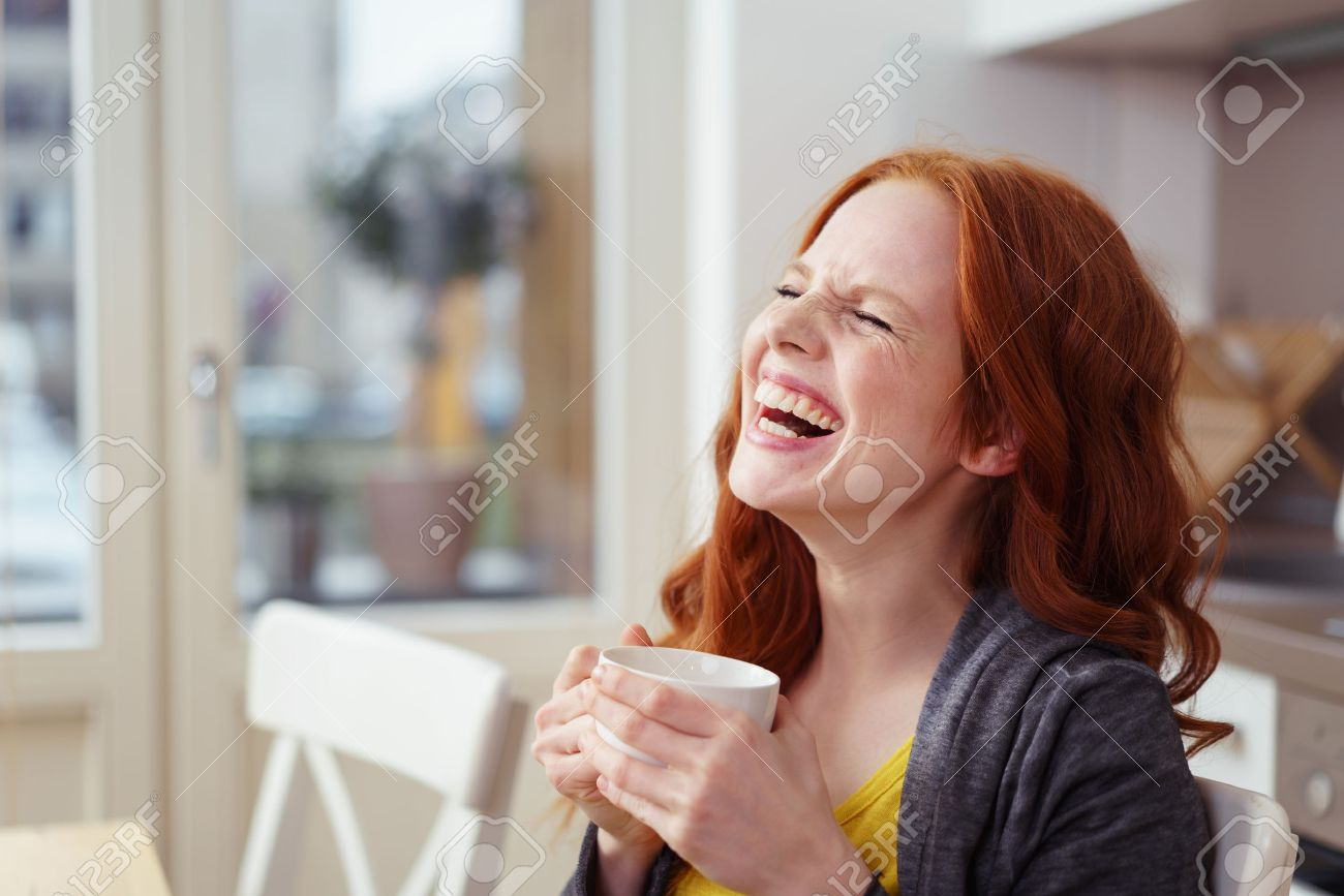 Spontaneous attractive young redhead woman enjoying a good laugh over a morning cup of coffee at home in the apartment - 54149205