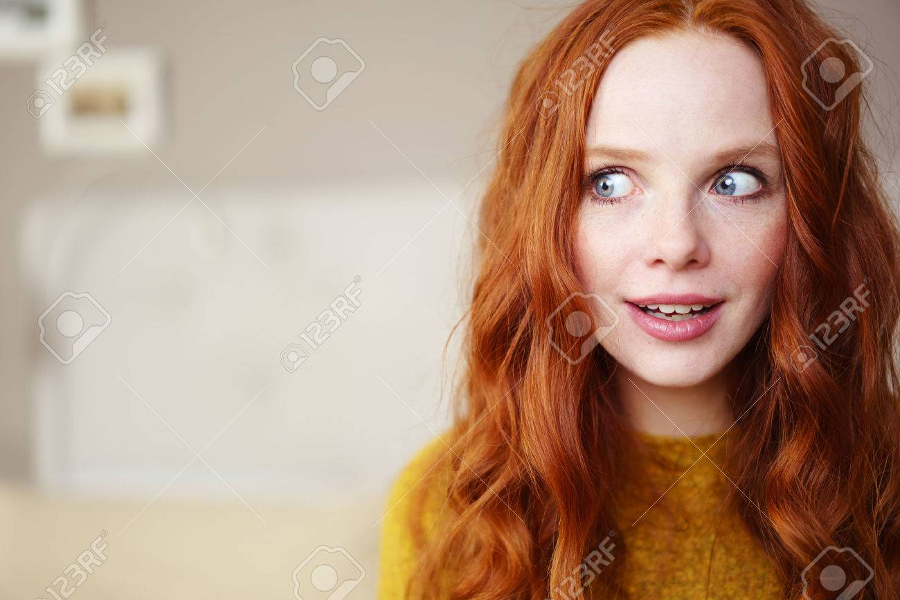 Head and Shoulders Portrait of Young Woman with Long Red Hair Wearing Yellow Sweater and Looking to the Side Playfully in Bedroom with Copy Space Banque d'images - 54149292