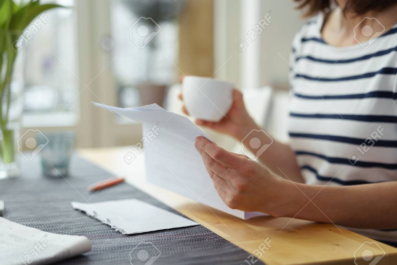 Woman reading a document at the dining table as she enjoys a morning cup of coffee, close up view of her hands - 54149378