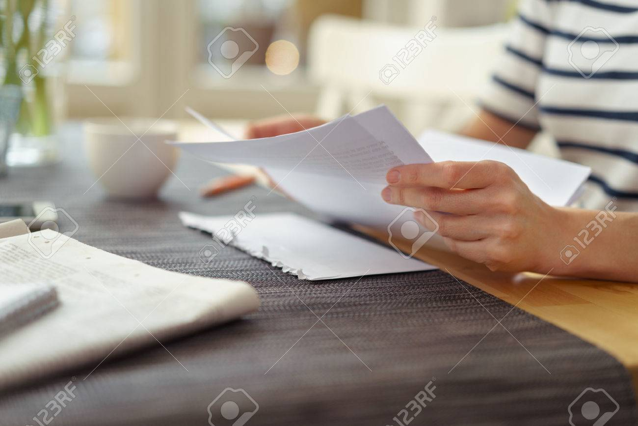 Person seated at a table with a cup of coffee reading a paper document, close up view of the hands Stock Photo - 54149404