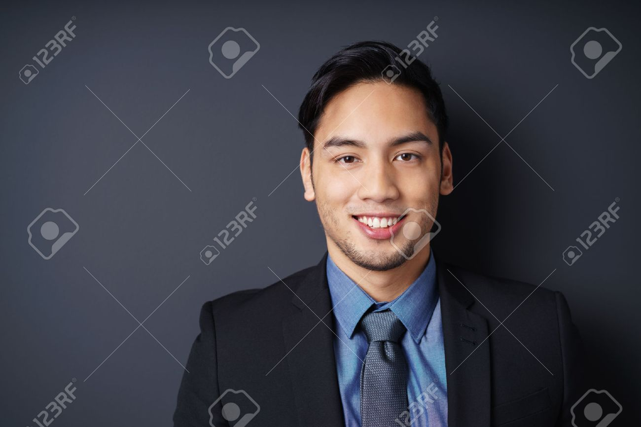 Close up of smiling single young bearded male manager in blue jacket, shirt and necktie with copy space in dark background Banque d'images - 54149569