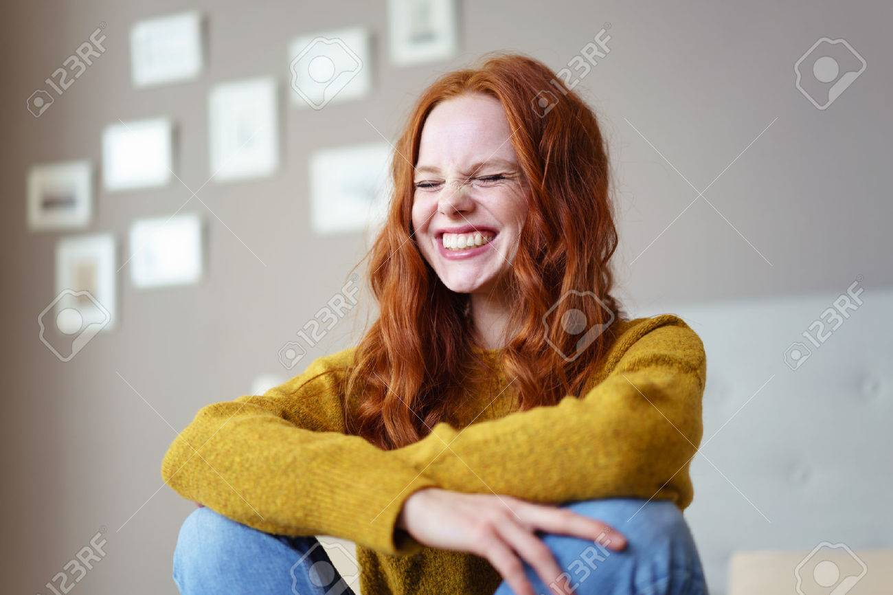 Pretty vivacious young woman laughing with her eyes screwed closed in a candid moment of fun and hilarity as she sits on her bed at home Banque d'images - 54149564