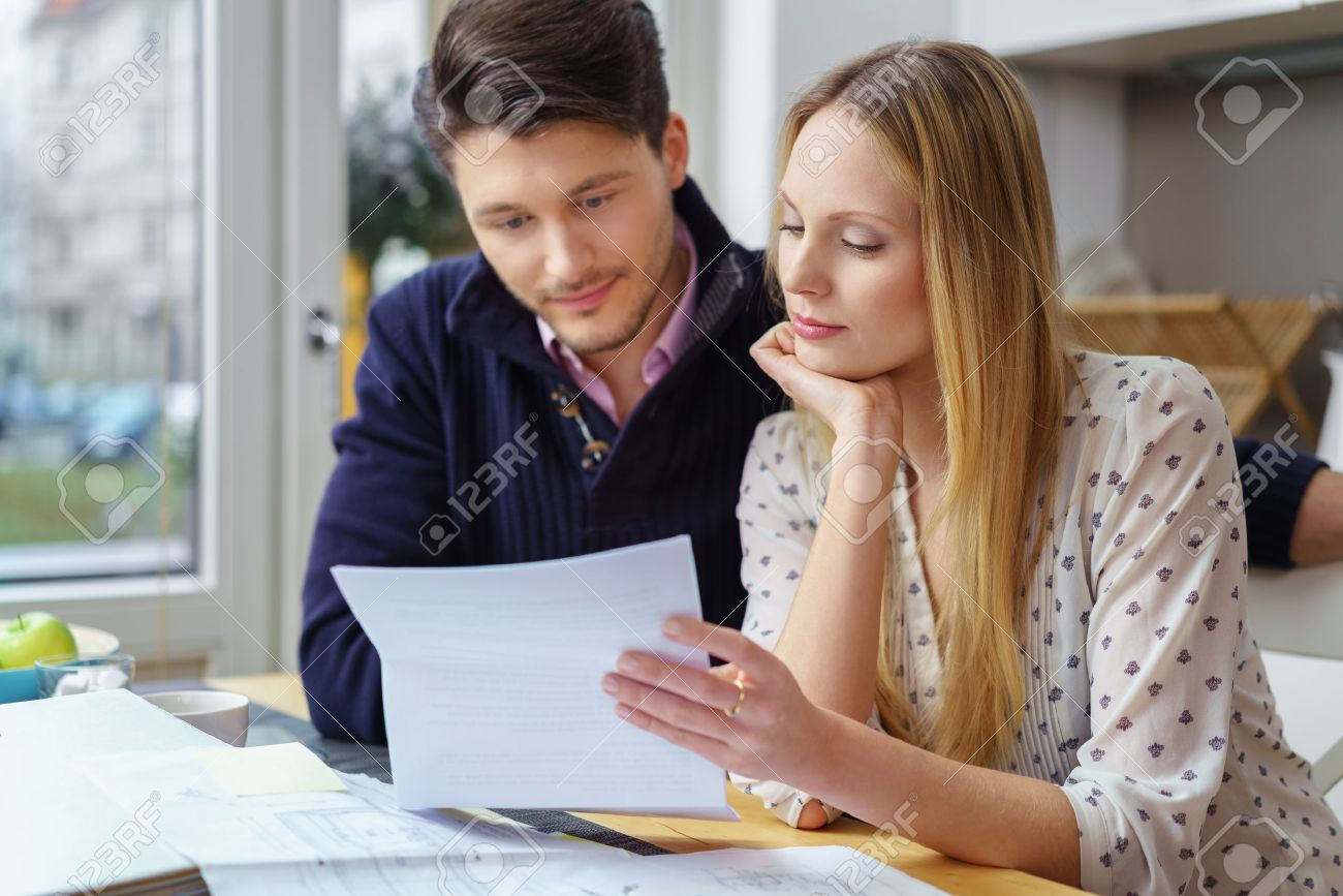 Handsome young man with mustache and beautiful woman with long hair at table looking at documents in kitchen next to window - 54150226