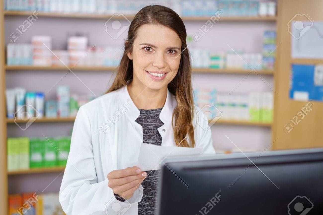 Single young pharmacy technician in long brown hair and white lab coat entering prescription order on computer with medications on shelf in background Banque d'images - 54157361