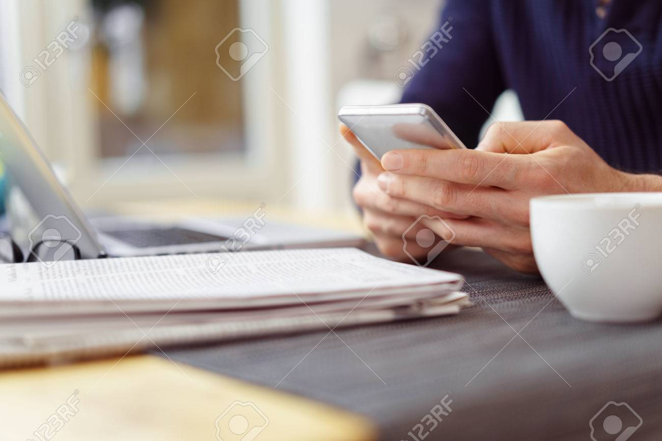 Man texting on his mobile phone as he sits at the table at home with an open newspaper in front of him Banque d'images - 54556929