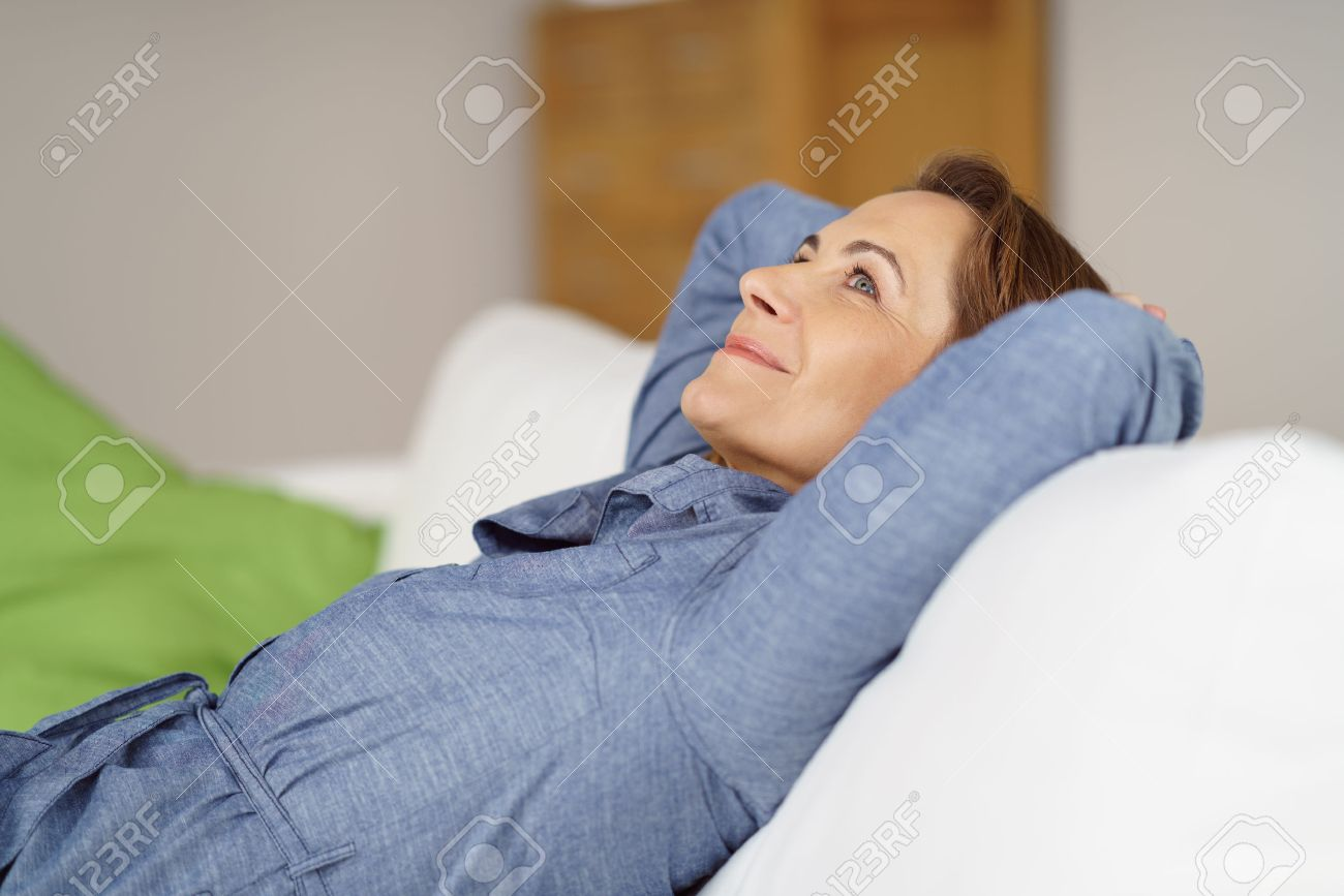 Happy Middle Aged Woman Relaxing At Home Reclining On A Comfortable Sofa  With Her Hands Behind