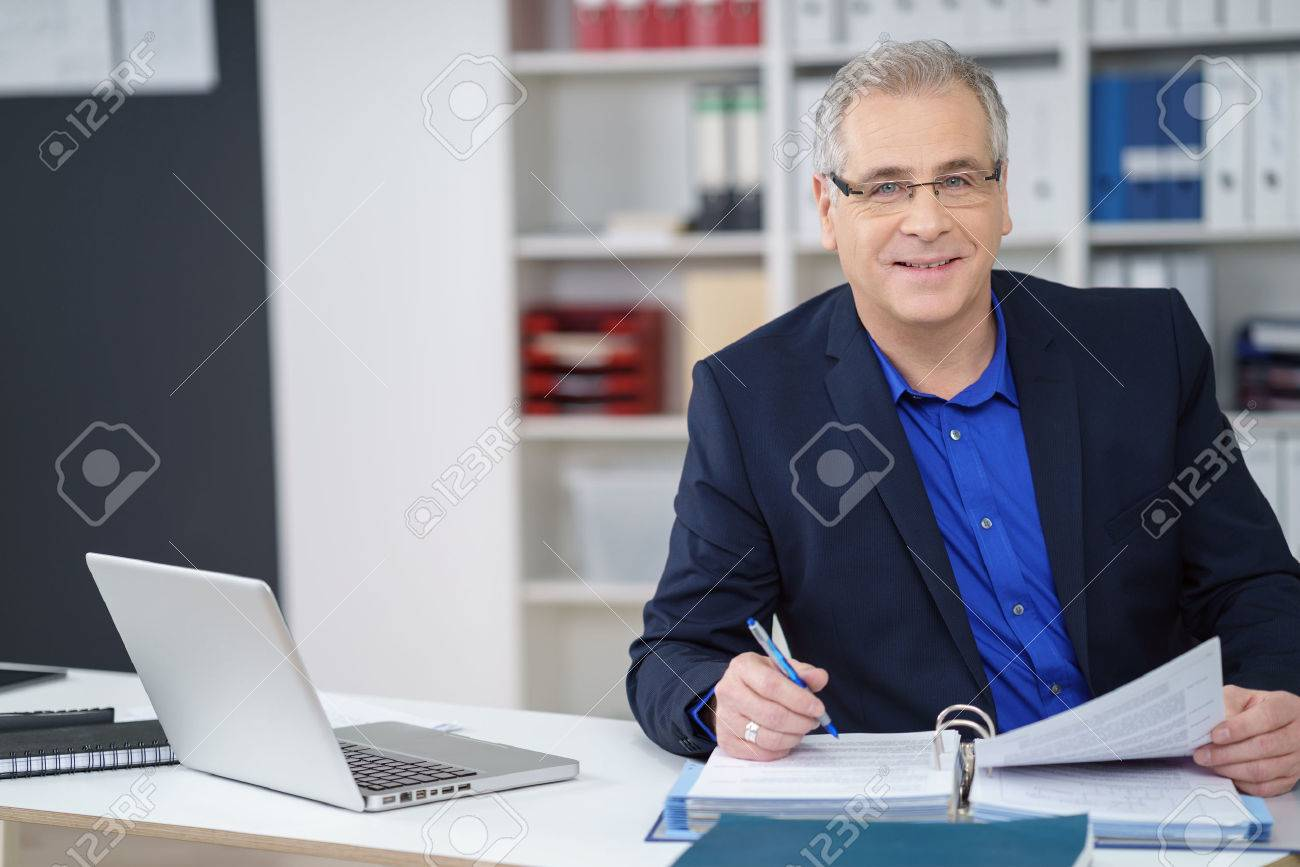 Business executive wearing glasses sitting working at his desk on paperwork in a binder looking at the camera with a smile Banque d'images - 55232685