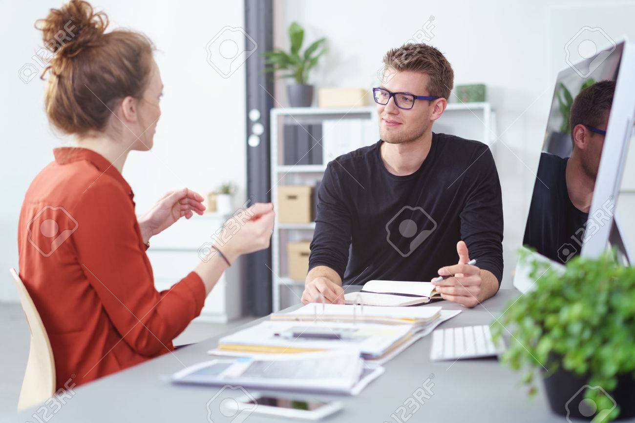 Young businessman and woman in a meeting having an animated discussion as they sit together at a desk, focus to the young man wearing glasses Banque d'images - 55665992