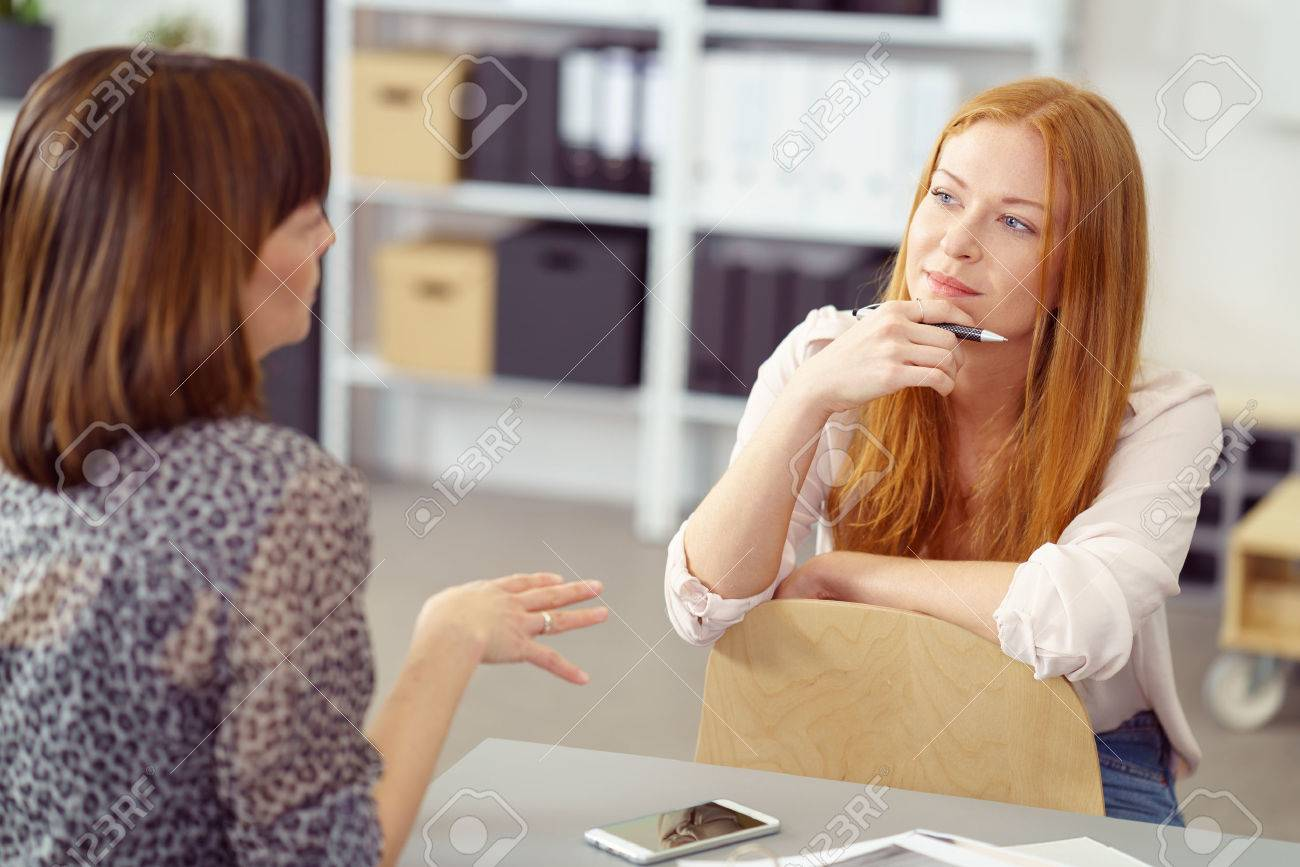 Two businesswoman having an informal meeting with one sitting relaxing on a reversed chair listening to her colleague with a pensive expression Standard-Bild - 55666000