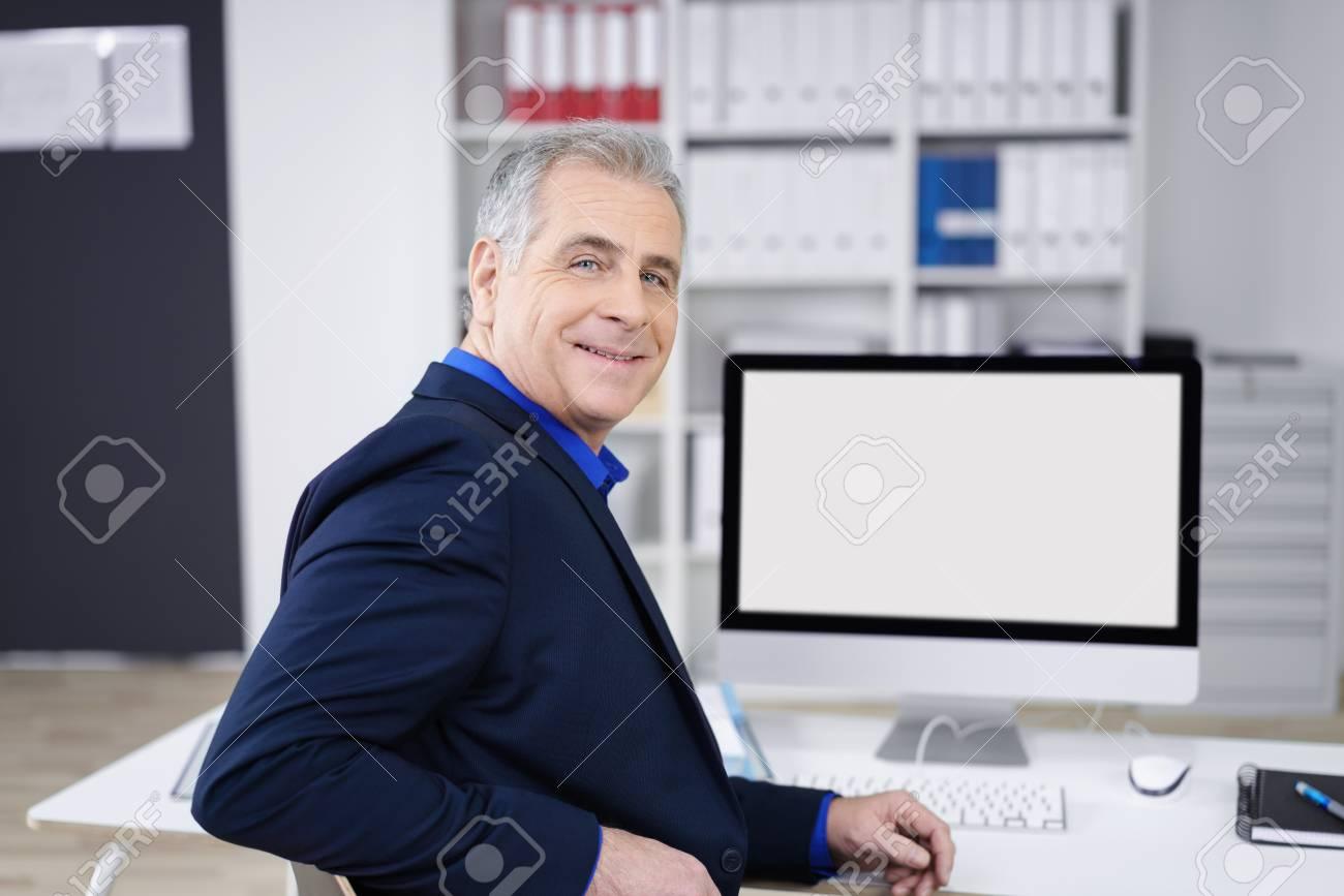 Homme daffaires dâge moyen tournant dans sa chaise au bureau pour