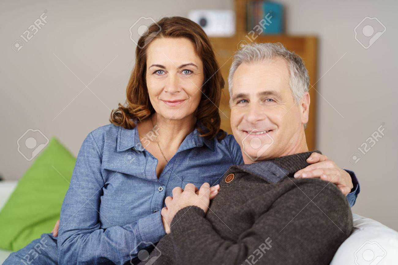 Attractive middle aged male and female couple holding hands together on sofa next to green pillow in living room Banque d'images - 56708803