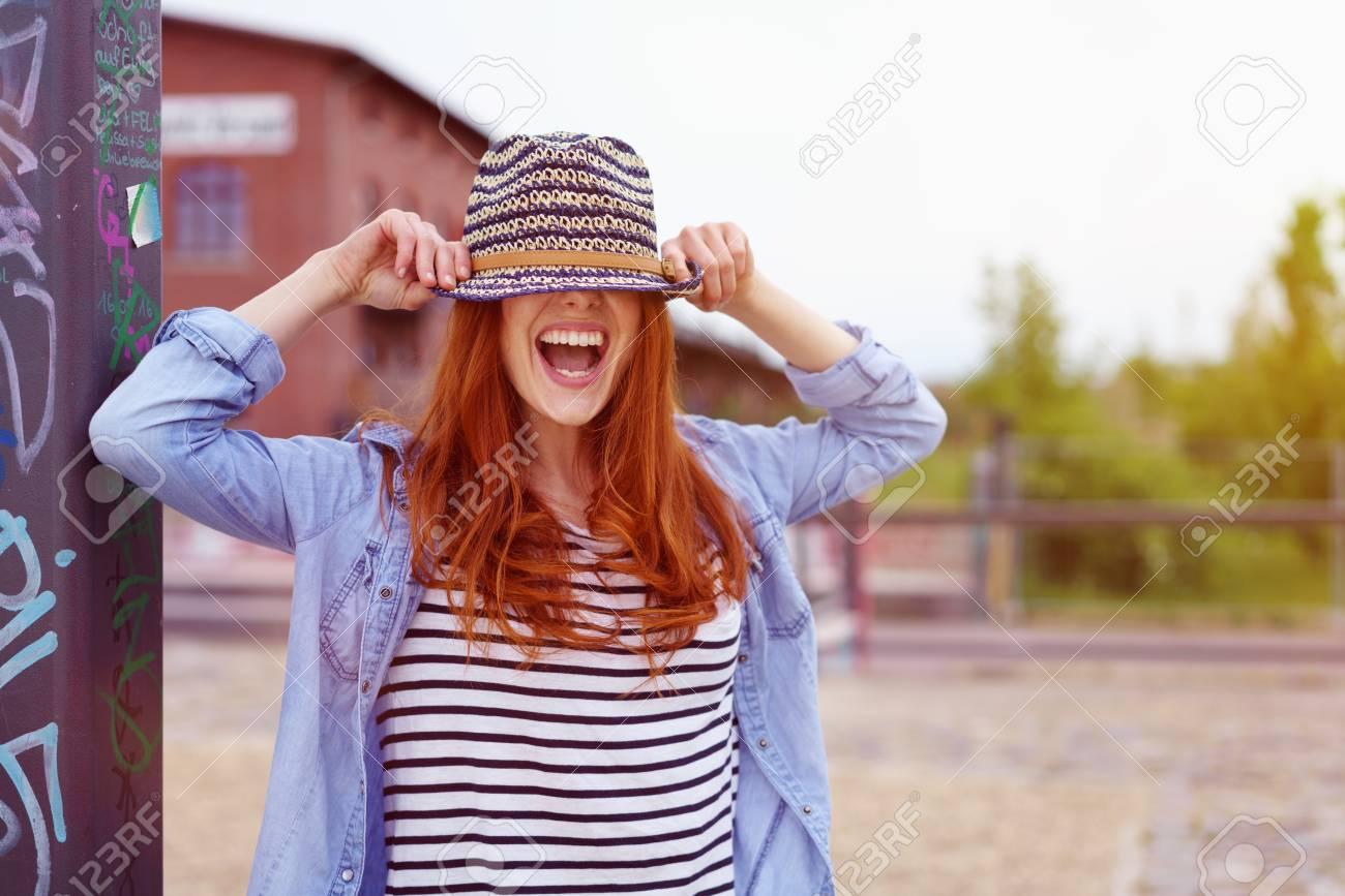 grande variété de styles meilleur choix nouveau authentique Rire de la femme ludique qui se cache sous un chapeau de paille à la mode  qu'elle a tiré sur ses yeux alors qu'elle se tient dans un parc urbain en  ...