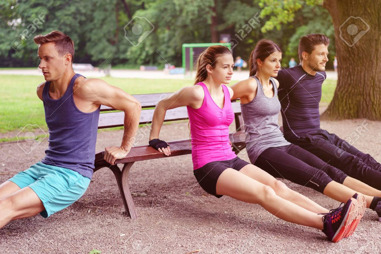 Group of four male and female adults performing dip exercises on park bench outdoors during summer Stock Photo - 59886624