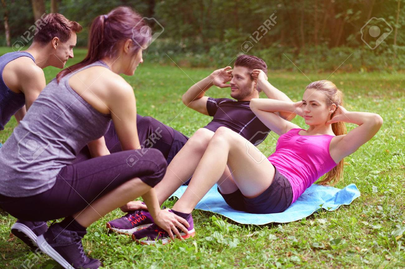 Two young couples working out in a park with one couple doing sit ups assisted by the second man and woman holding their feet - 61146892