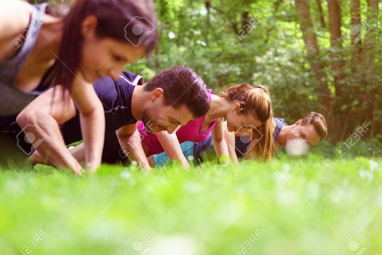 Four young people doing push-ups in a park during a fitness workout viewed very low angle across the grass - 59886791