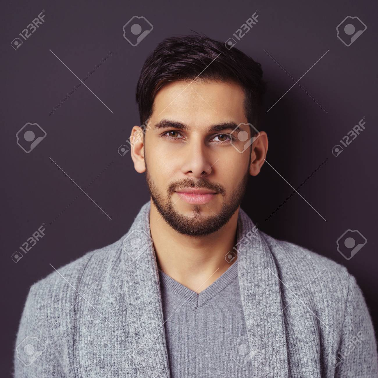 Thoughtful handsome bearded young man staring pensively at the camera in a stylish grey sweater and top, closeup head and shoulders square format - 61146943