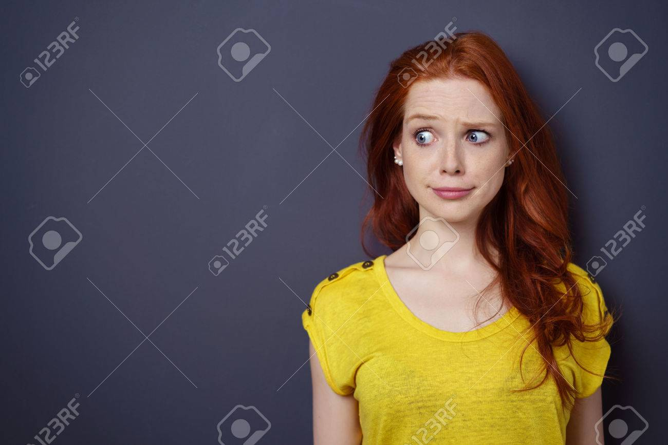 Single gorgeous young long haired woman in yellow shirt with puzzled or worried expression over simple dark background with copy space - 61147153