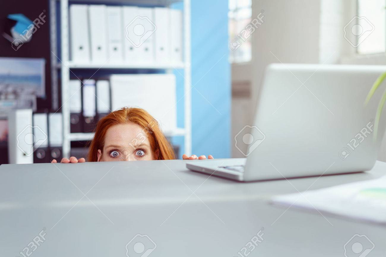 Young businesswoman peering over her desk in the office in wide eyed horror or amazement with just her eyes visible Banque d'images - 61147159