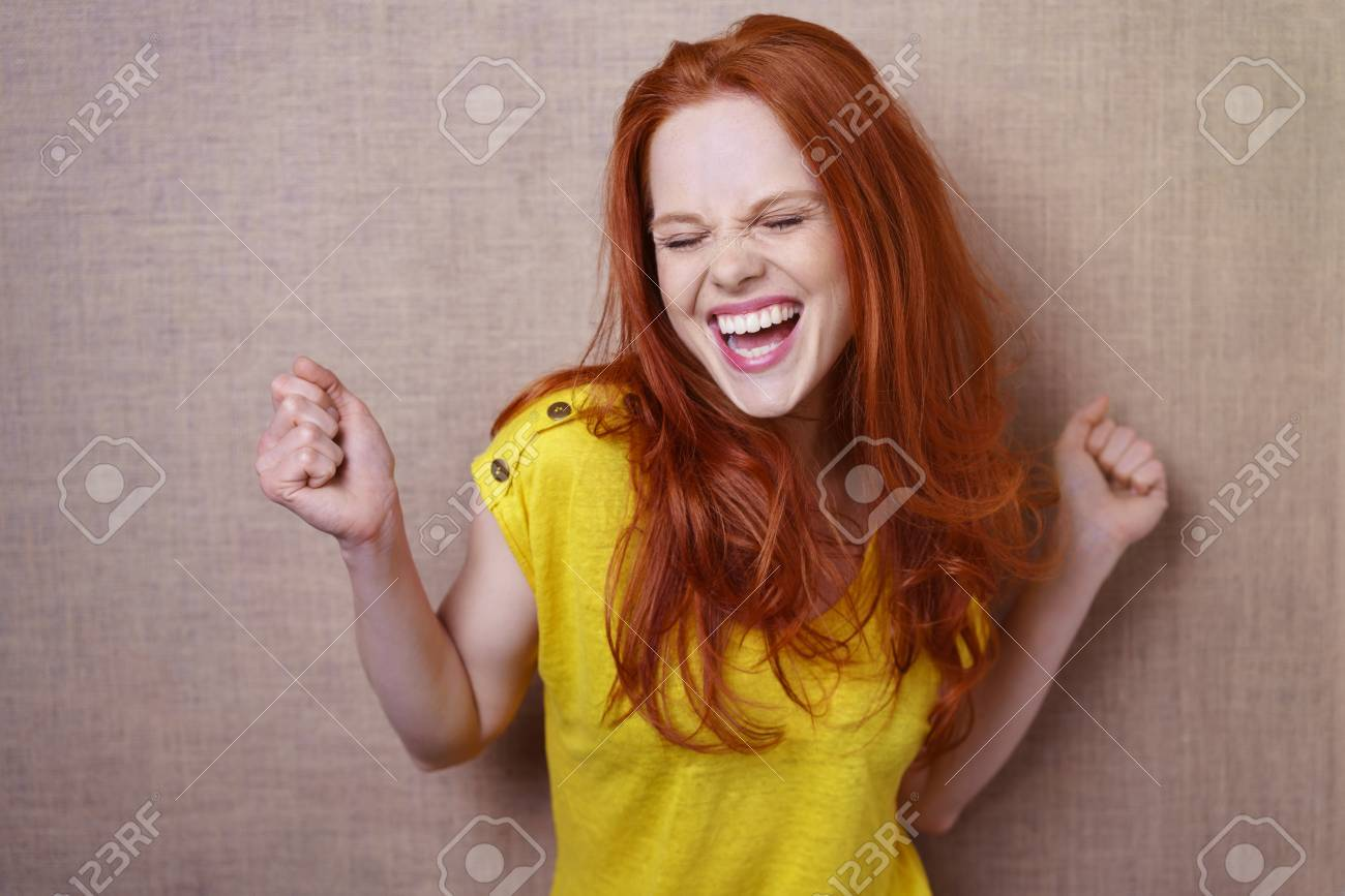 Single gorgeous young red haired woman in yellow shirt dancing or rejoicing about something over simple brown cloth background with copy space - 63935682
