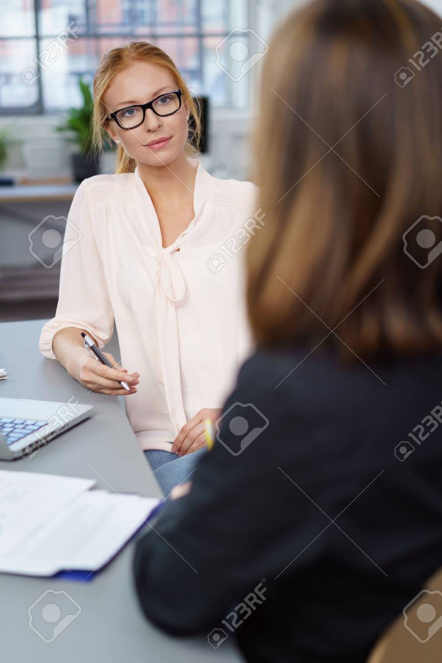 Two female business colleagues in a meeting sitting at a table in the office having a serious discussion Standard-Bild - 61071926