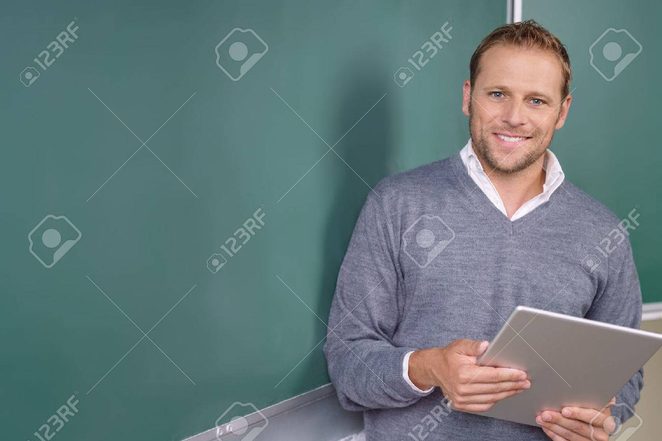 Happy friendly young teacher or pst graduate male student standing holding a tablet in front of a blank chalkboard Banque d'images - 62901996