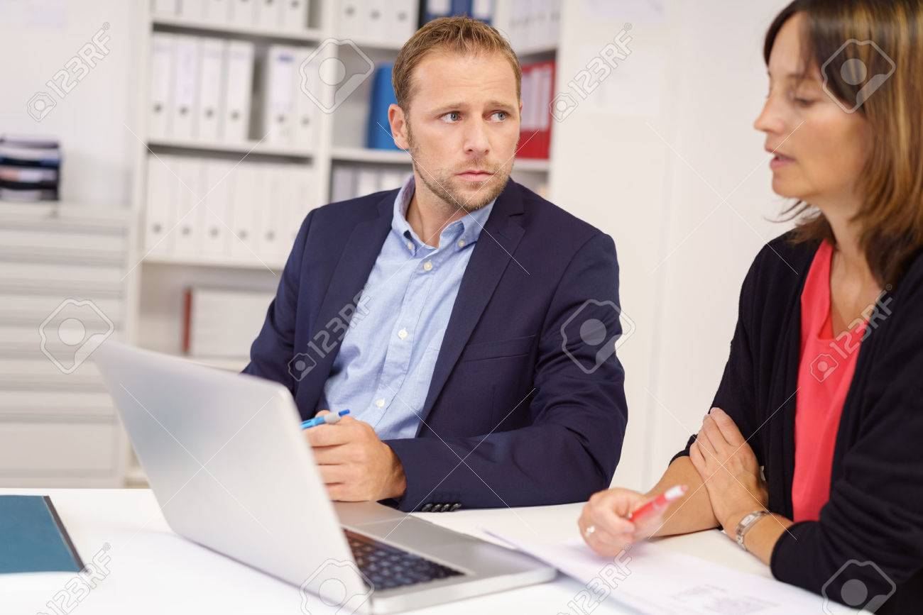 Worried businessman listening to a middle-aged female colleague as they sit together at a table in the office sharing a laptop computer Banque d'images - 61620752