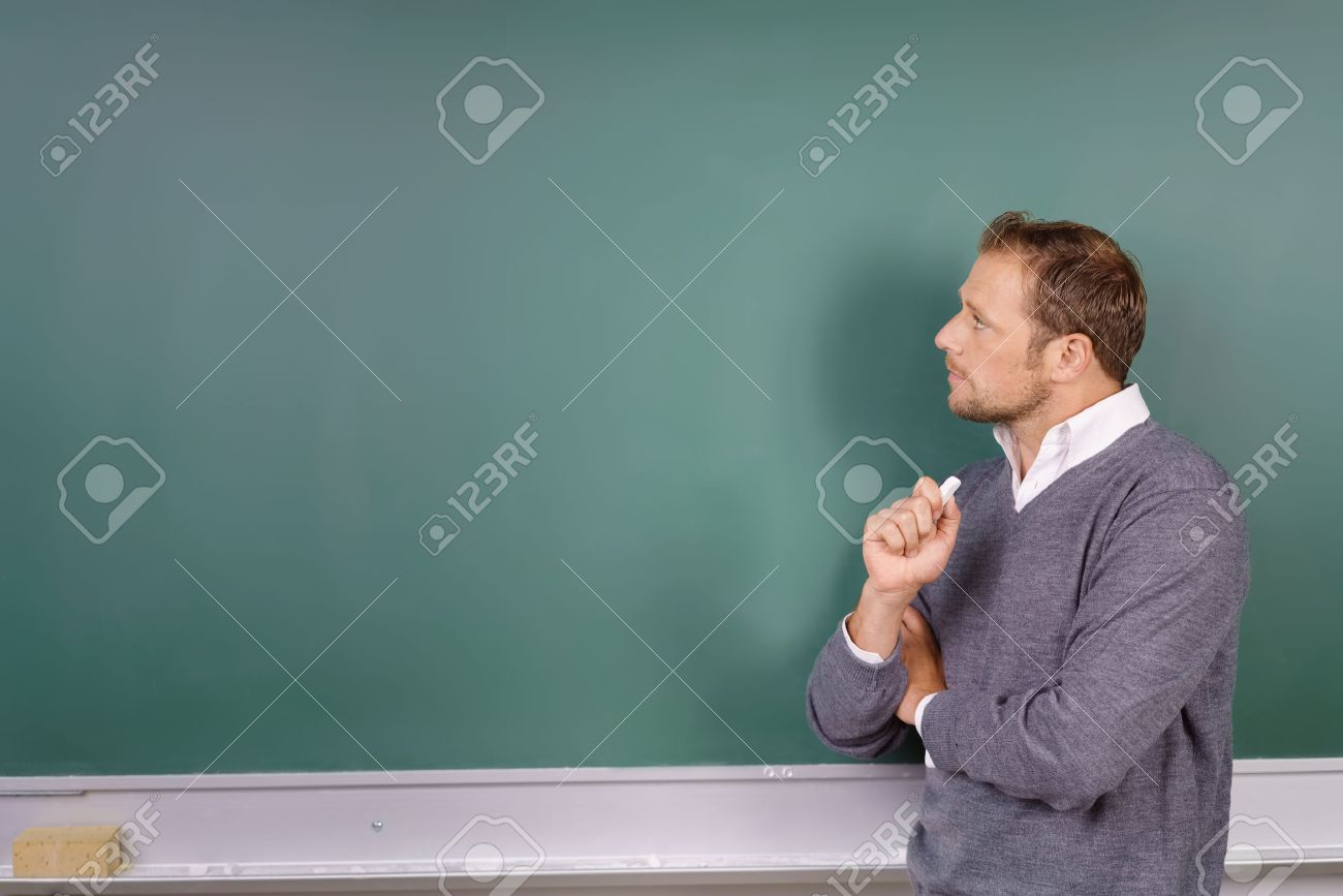 Thoughtful male teacher looking at a blank empty green blackboard with a stick of chalk in his hand and copy space for your text - 62901998
