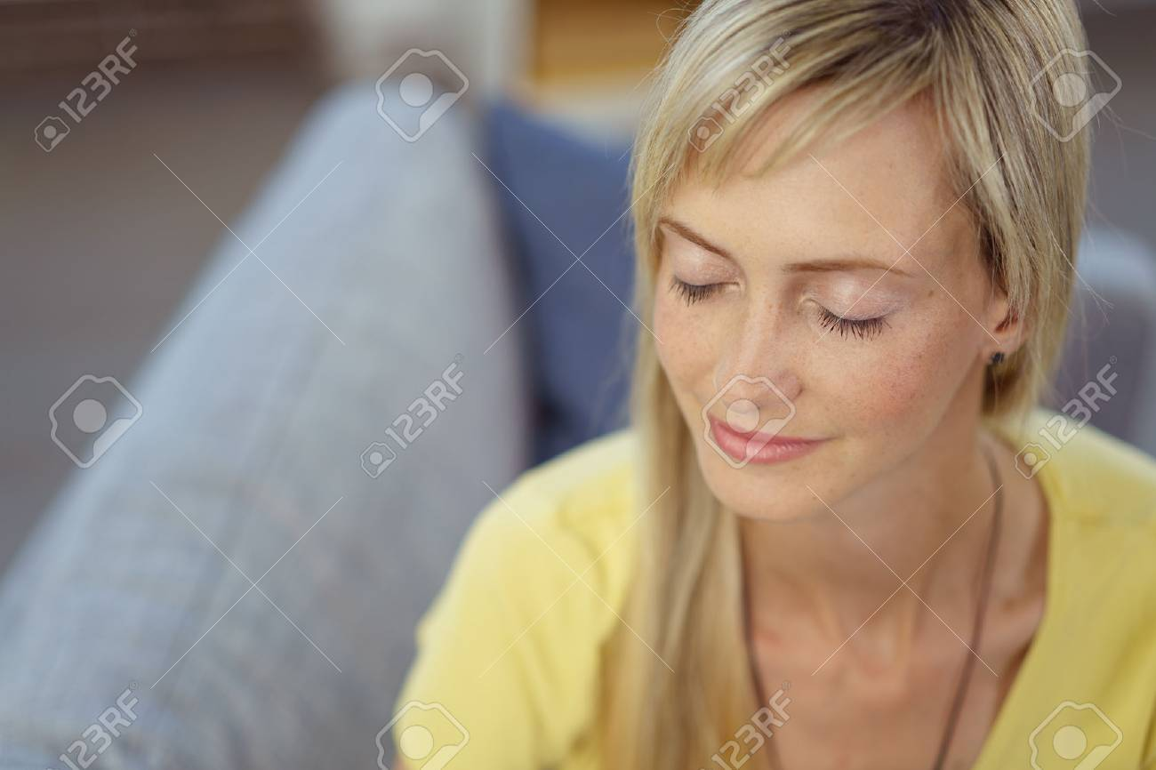 Attractive young blond woman taking a quiet moment to herself sitting relaxing on a sofa at home with closed eyes - 64914638