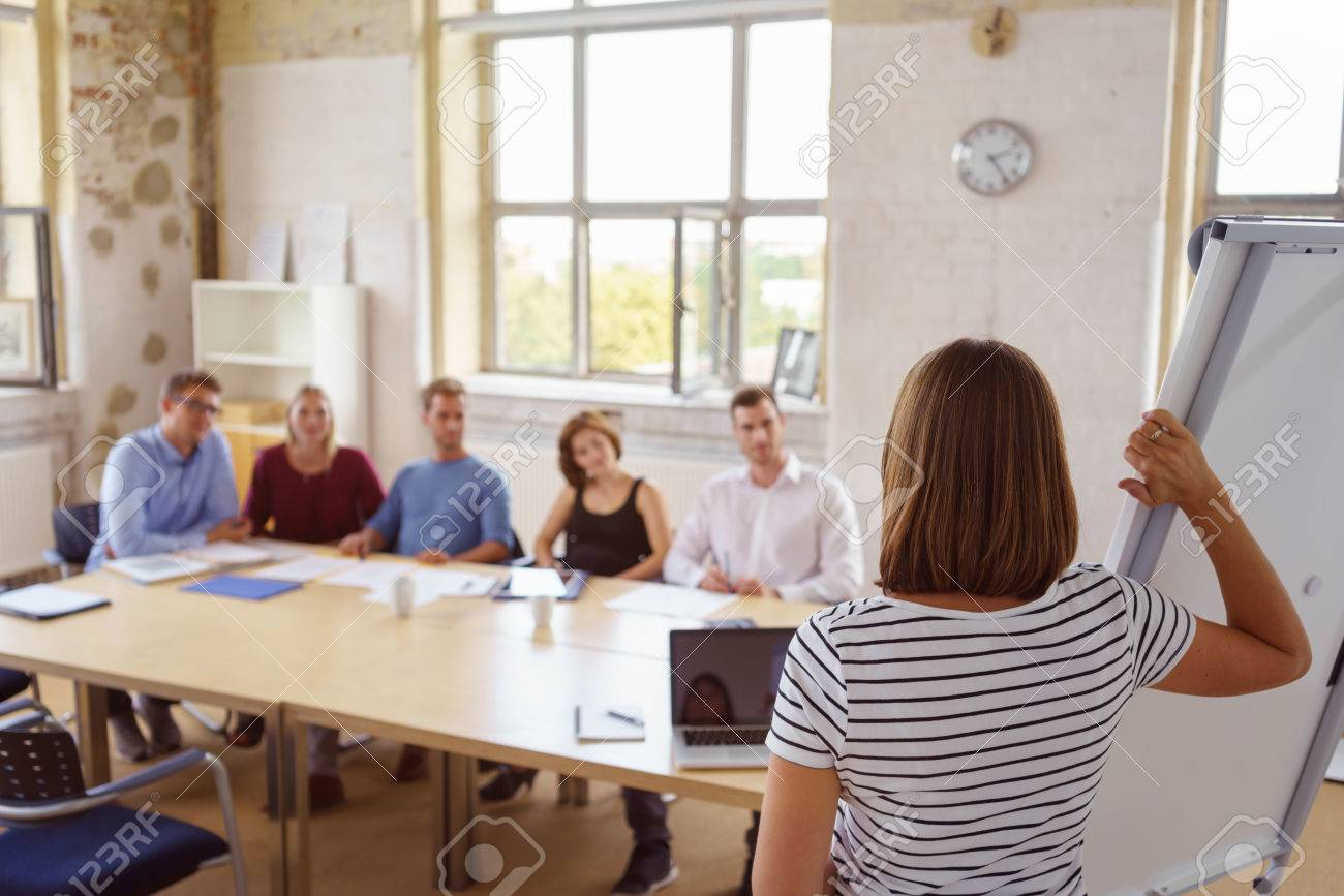 View from behind a businesswoman standing at a flip chart giving a presentation to colleagues seated at a conference table - 63969574
