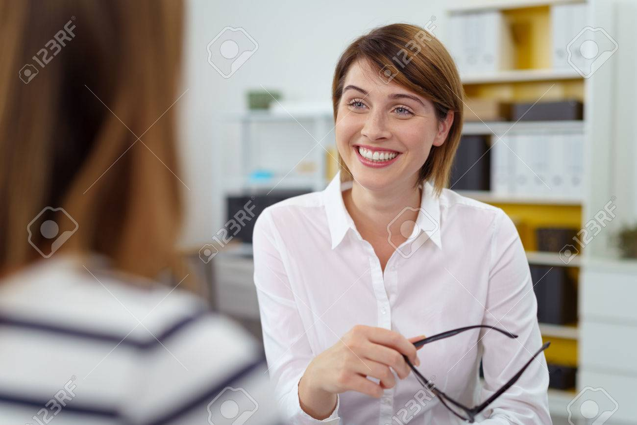 Woman holds her glasses in one hand while smiling at her associate as they talk in the office Banque d'images - 65435696